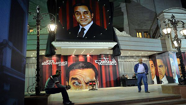 A picture taken on January 22, 2013 shows Egyptians walking past posters of Egyptian satirist Bassem Youssef outside a theatre in Cairo. (AFP)