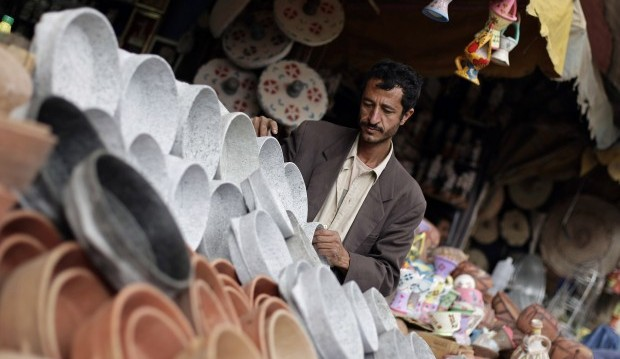 A Yemeni man works on the display of his wares in his shop at a market in the old city neighborhood of Sanaa, Yemen, Sunday, March 24, 2013. (AP Photo/Hani Mohammed)